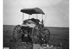 Reverend Robert Mitchell, agent for the Smith of Dunesk Mission at Beltana, taking a rest beside his mud caked buggy cart vehicle' on his first posting to the mission. Date: about 1897